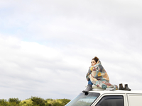 Young woman sitting on the roof of a white van wrapped in patterned blanket