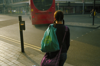 Rear view of young woman carrying bags standing by bus stop. Battersea, London, England, United Kingdom