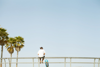 Rear view of skateboarder sitting on railing at skate park. Los Angeles, U.S.A