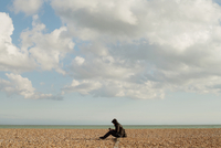 Man on beach reading. Brighton, England, United Kingdom