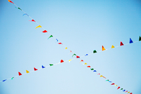 Colourful bunting hanging in a cross shape against a blue sky. Brighton, England, United Kingdom