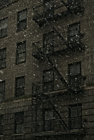 Snow falling in front of old brick apartment building. Brooklyn, New York, U.S.A