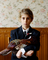 Portrait of a boy holding a pheasant