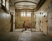 Prisoner sitting opposite a blurred visitor in a cell