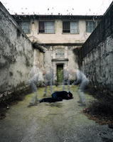 Man surrounded by blurred prisoners in prison courtyard