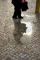 Pedestrian reflected in puddle on cobble street. Lisbon, Portugal