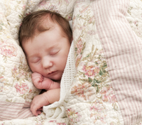 Baby asleep under a floral pattern blanket