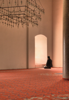 Man kneeling and praying in a mosque in front of a window