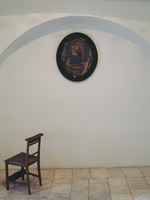 Religious icon and empty chair against a white wall in a church. Italy
