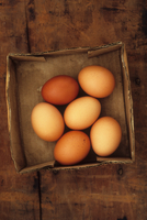Six eggs lying in old cardboard box on wooden table