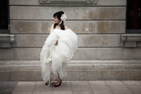 Young woman holding wedding dress in street. Shamian Island, Guangzou, Guangdong, China