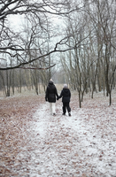 Young woman and girl walking through a wintry forest holding hands