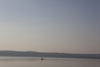 Canoeist on calm lake. Lake Bolsena, Italy