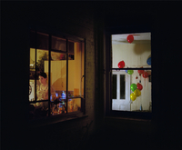 Woman standing in the kitchen by the window at night with adjacent room filled with balloons