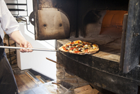 Pizza being taken out of oven on old fashioned oven. Somerset, England, United Kingdom