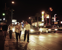 People walking on road at night in Los Angeles, California, USA
