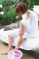 テラスでフットケアをする女性と寝転ぶネコ 21001000170| 写真素材・ストックフォト・画像・イラスト素材|アマナイメージズ