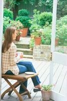 テラスで椅子に座ってくつろぐ女性