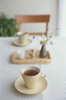花を飾ったテーブルの上のコーヒーカップ