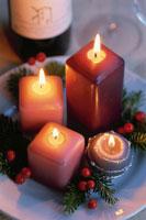 赤い実を飾ったクリスマスキャンドル4つ 21002000503| 写真素材・ストックフォト・画像・イラスト素材|アマナイメージズ