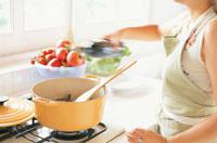鍋で料理を作る女性