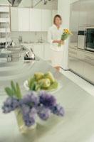 キッチンで花を持って歩く女性