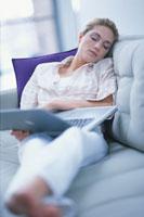 ノートPCを広げたままソファで眠る女性