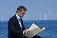 新聞を読むビジネスマンと風車