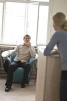 女性とイスに座る男性 21005000845| 写真素材・ストックフォト・画像・イラスト素材|アマナイメージズ