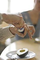 アボカドに塩をかける男性の手元