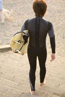 ウエットスーツを着てサーフボードを持つ男性