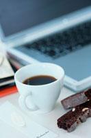 コーヒーの入ったカップとノートパソコン