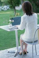 パソコンに向かう女性の後姿 21006000187| 写真素材・ストックフォト・画像・イラスト素材|アマナイメージズ