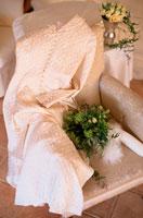 白いソファの上のドレスとフラワーアレンジメント 21006000277| 写真素材・ストックフォト・画像・イラスト素材|アマナイメージズ
