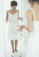 体重計に乗り驚く女性 21007000347| 写真素材・ストックフォト・画像・イラスト素材|アマナイメージズ