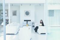 カラーを持ち白いソファに座る外国人女性