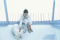 プールサイドで犬と遊ぶ女性