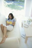 白いソファに横になり本を読む日本人女性