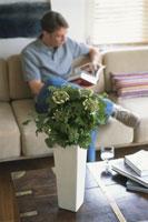 花を置いたテーブルとソファに座って本を読む男性