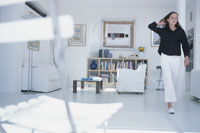 白いソファや本棚のあるリビングルームを歩く女性