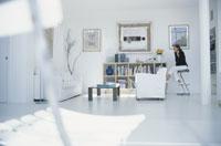 白いソファや本棚のあるリビングでイスに座る女性
