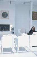 白いイスやソファセットのあるリビングで寛ぐ女性