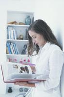 壁に寄りかかって本を読む女性と本棚