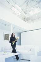 白いリビングルームの中で花束を持つ女性
