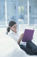 白いソファに座って本を読む女性