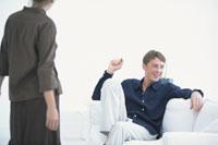 白いソファに座って笑う男性と前に立つ女性
