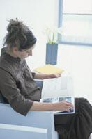 白いイスに座って本を読む女性