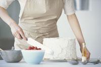 シフォンケーキにクリームを塗る女性