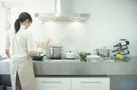 IHクッキングヒーターのシステムキッチンで料理する女性