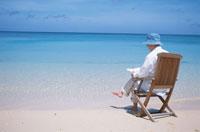 砂浜で本を読む男性